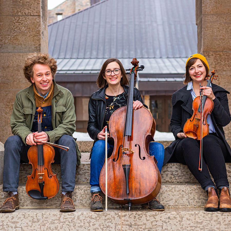 Indigo Trio members John Sellick, Alyssa Ramsey and Jessie Ramsey seated outdoors with their instruments