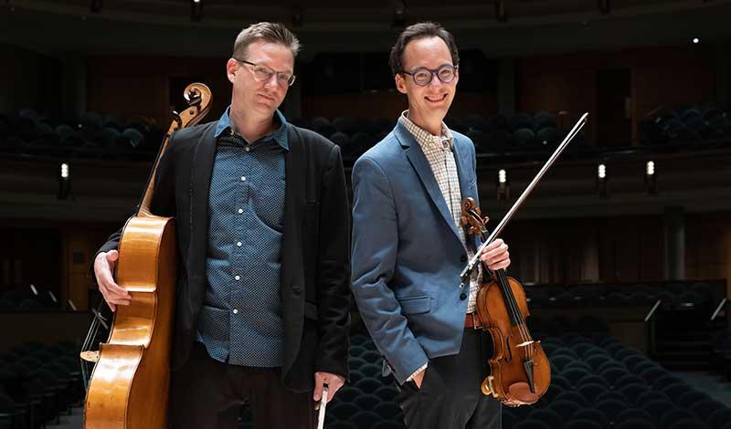 Violinist Robert Uchida and cellist Rafael Hoekman stand in a darkened theatre holding their instruments.